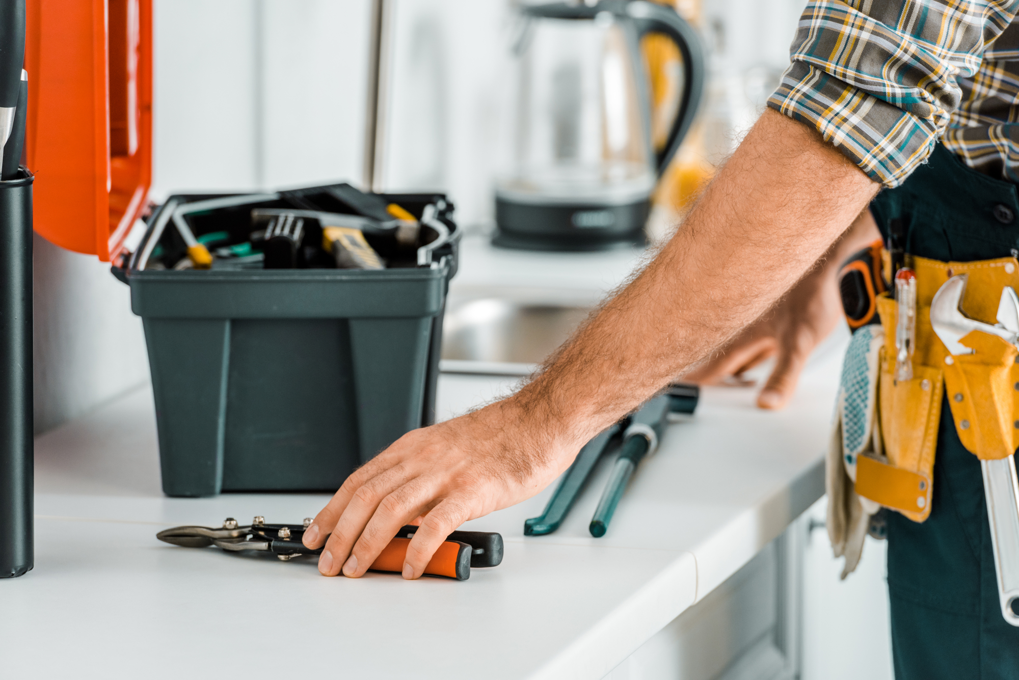 Cropped image of plumber putting tools on kitchen counter in kitchen