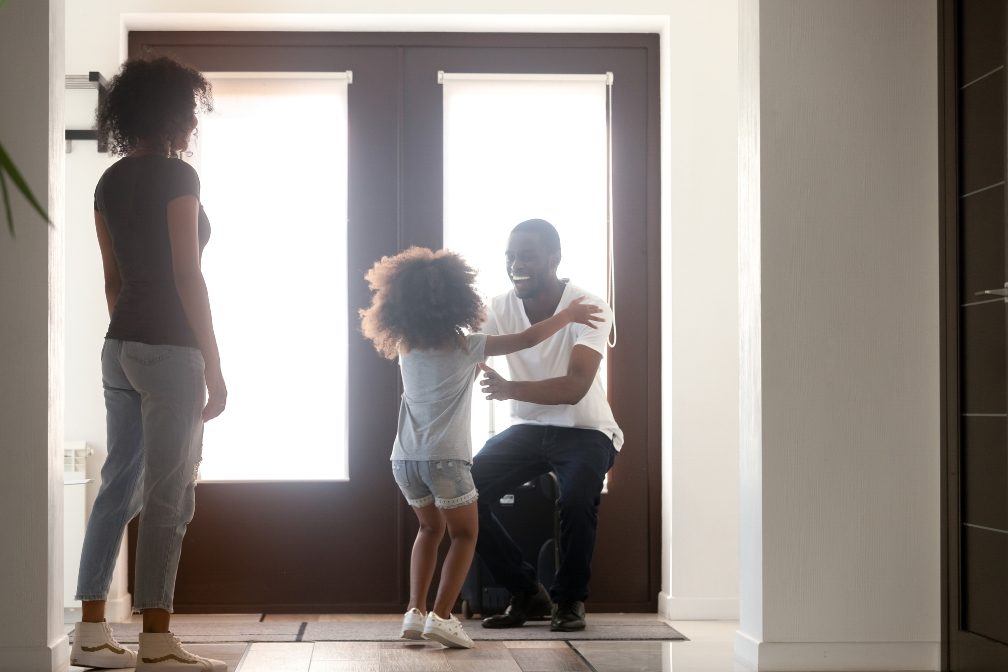 Happy kid daughter excited to meet african dad arriving home