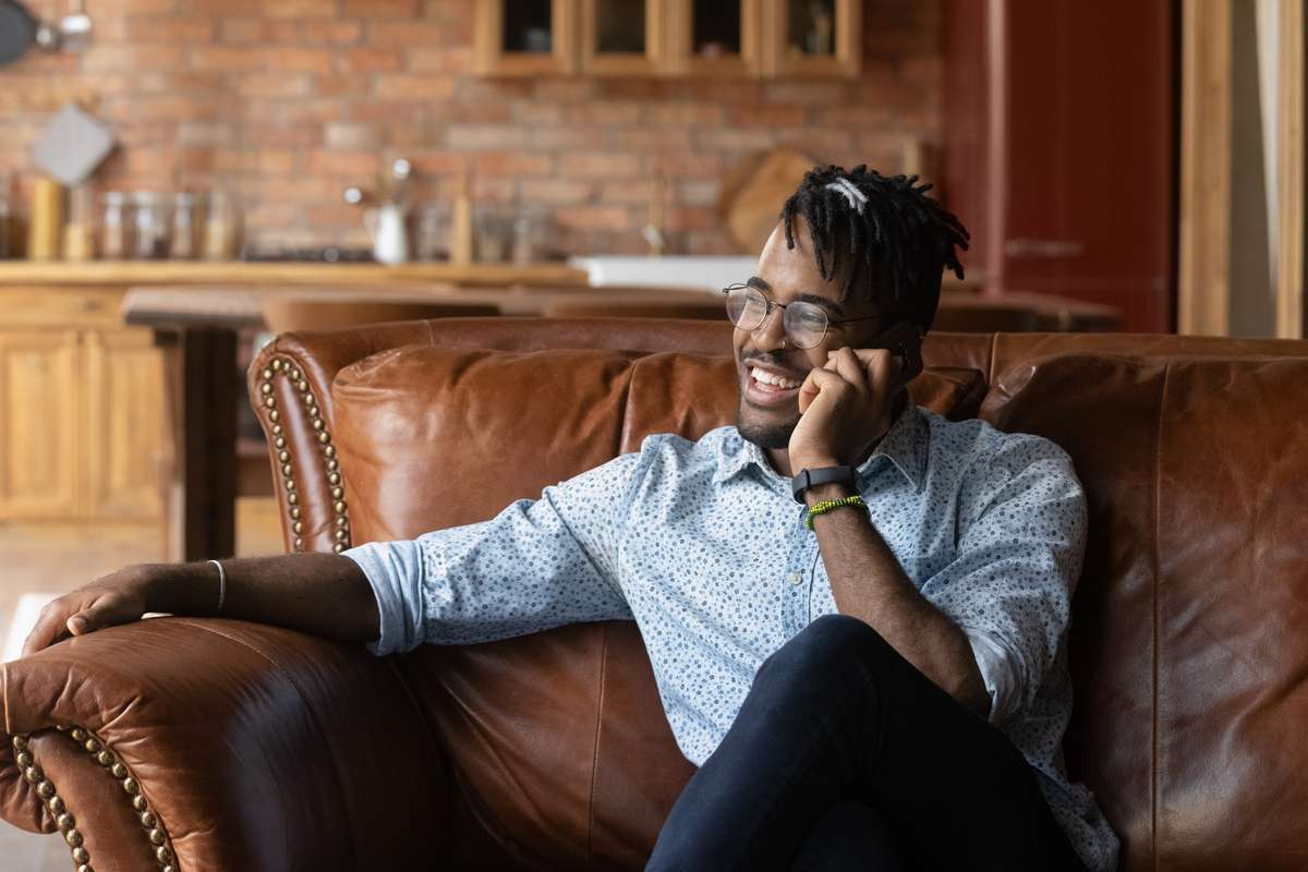 Happy thoughtful millennial Black hipster guy speaking on mobile phone (R) (S)