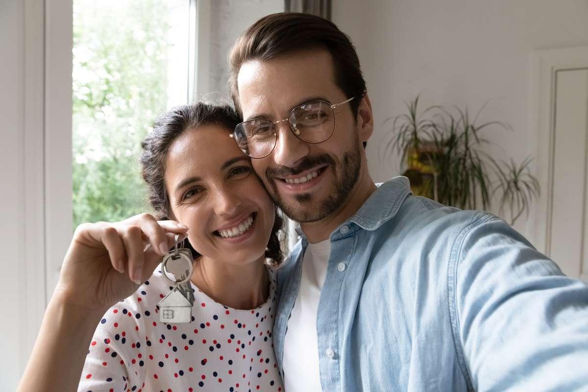 Head shot portrait wife and husband taking selfie, showing keys (R) (S)