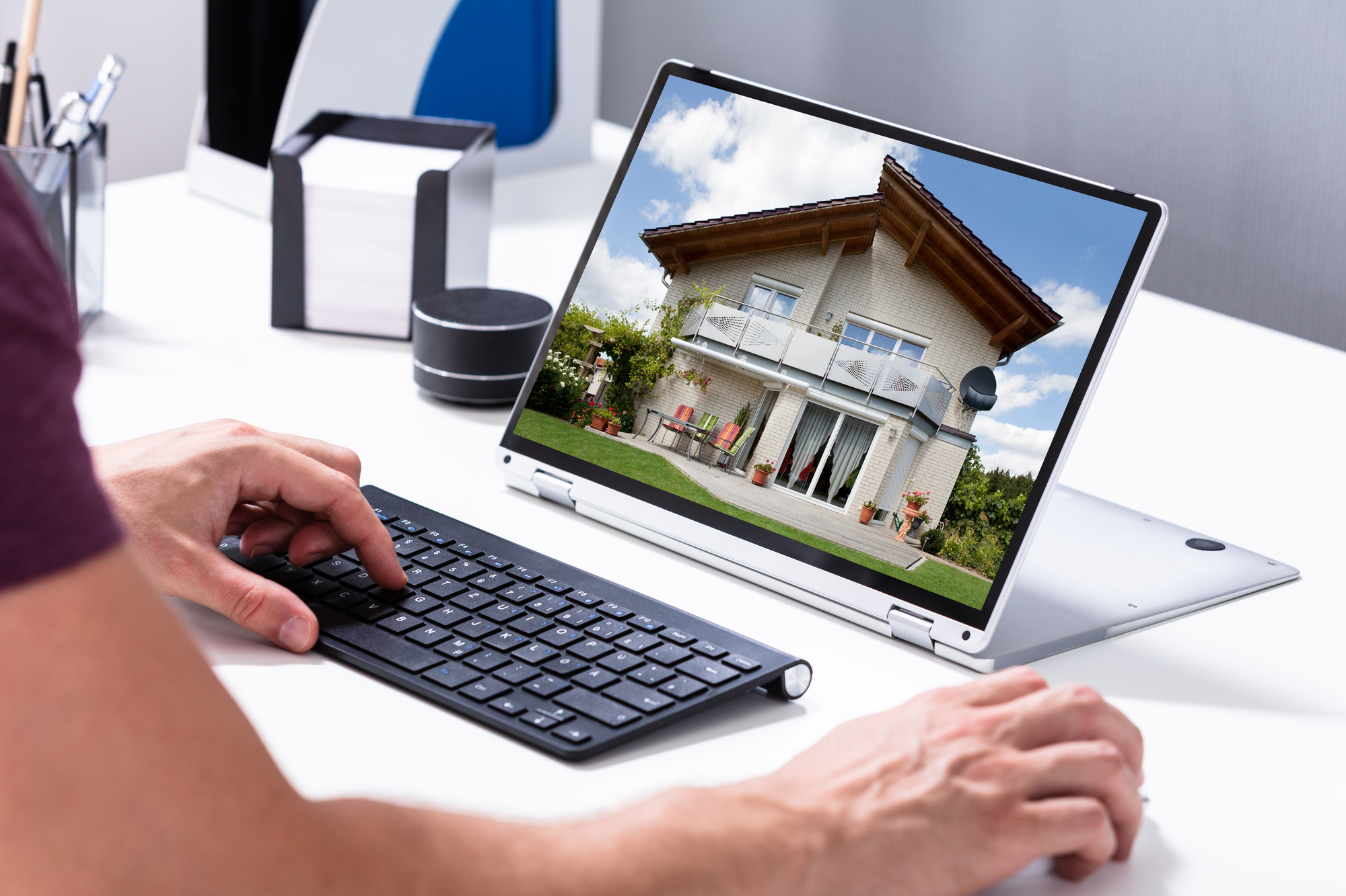 Man Selecting New House On Laptop At Home